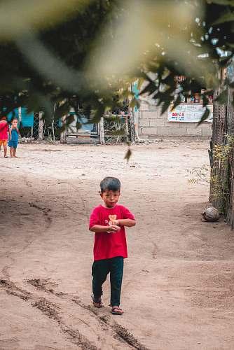 human boy in pink shirt walking on dirt person