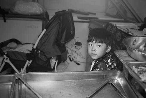 human boy sitting in kitchen black-and-white