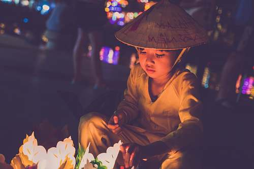 human boy wearing brown cap lighting candles during nightime person
