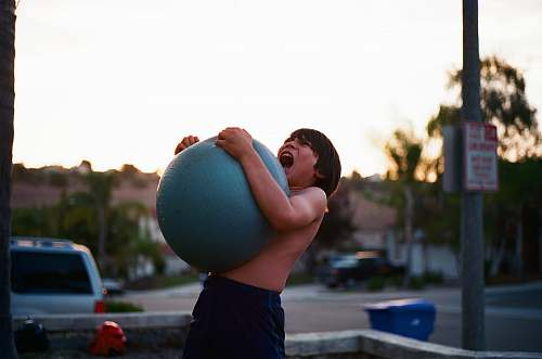 human boy's hugging yoga ball while opening mouth car
