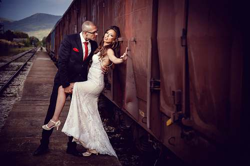 human bride and groom beside train during daytime person