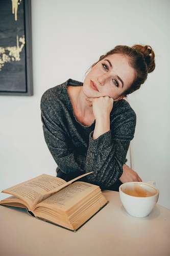 human brown-haired woman in black sweater near brown book person