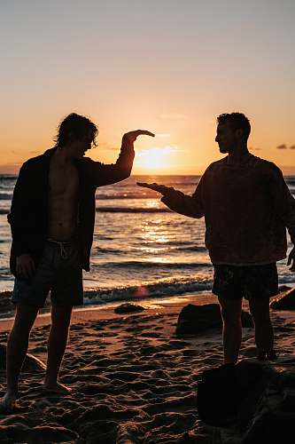 human close-up photo of two men shaking hands near beach at sunset person