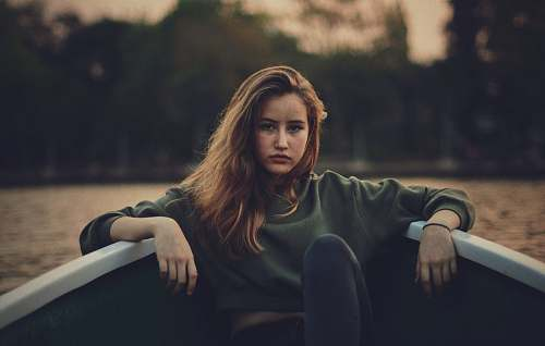 human closeup photography of woman wears green sweater on boat person
