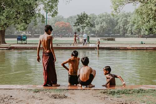 human four toddlers standing near body of water person