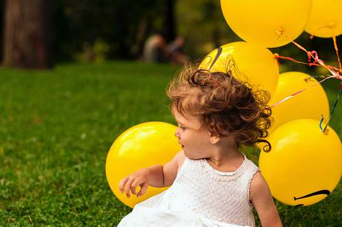 human girl sitting on grass near balloon person
