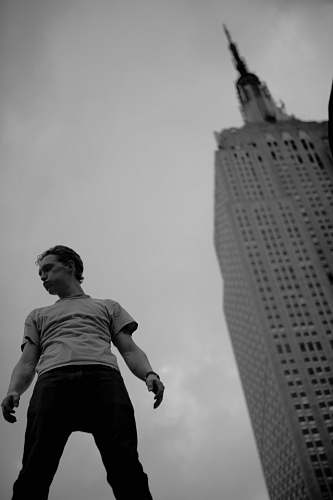 human grayscale low-angle photo of man standing near building black-and-white