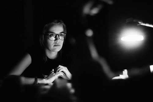 person grayscale photo of a woman wearing eyeglasses sitting in front of table black-and-white