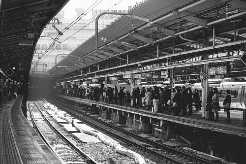 human grayscale photo of group of people walking in train station black-and-white