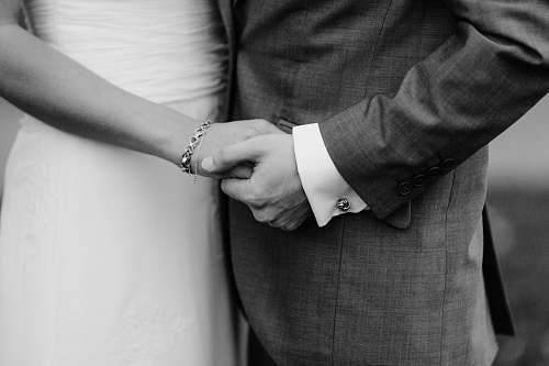 human grayscale photo of man and woman holding each others hands black-and-white