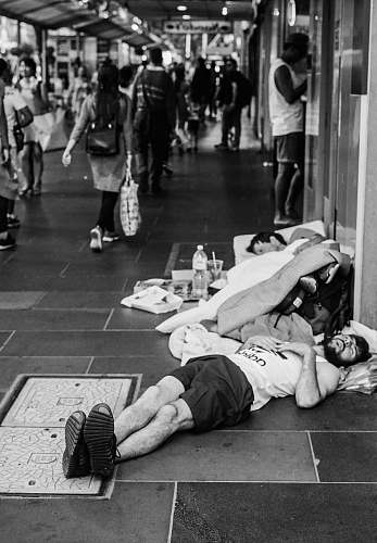 human grayscale photo of man sleeping on street black-and-white