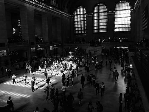 human grayscale photo of people walking inside the building black-and-white