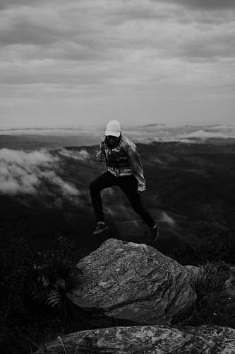 person grayscale photo of person jumping on rock black-and-white