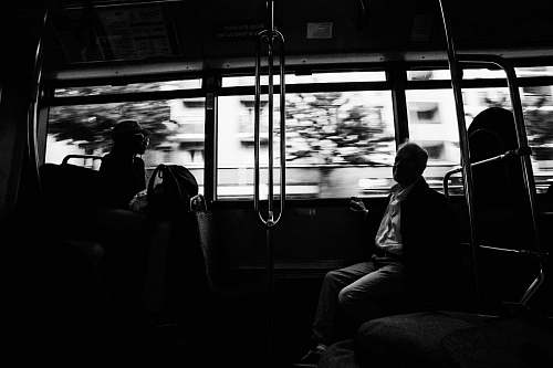 person grayscale photo of several people on moving train black-and-white