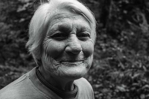 black-and-white grayscale photo of smiling woman in crew-neck T-shirt face