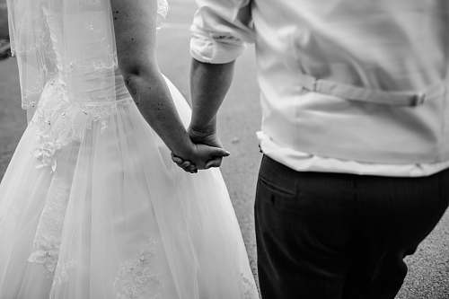 human grayscale photo of wedded couple holding hands black-and-white