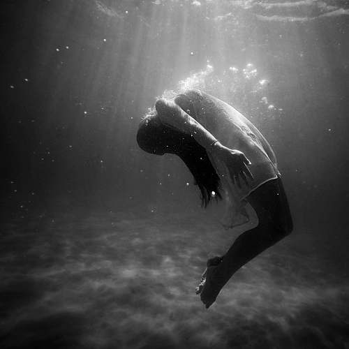 black-and-white grayscale photo of woman drowning in water grey