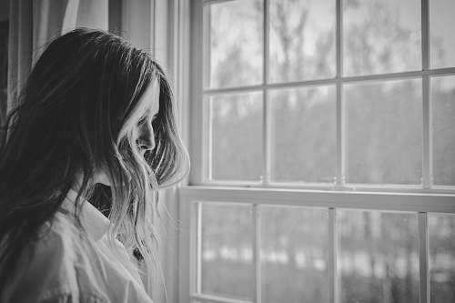 person grayscale photo of woman near window black-and-white