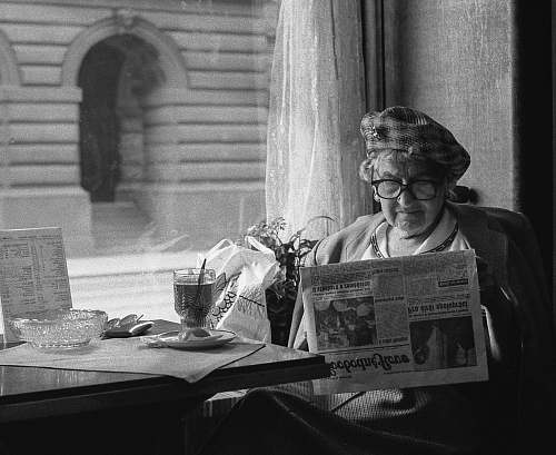 black-and-white grayscale photo of woman sitting while reading newspaper newspaper