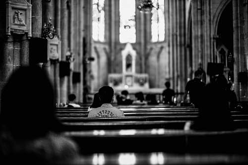 person grayscale photo of wooden pew black-and-white