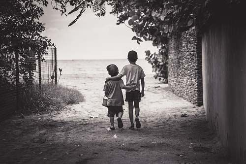human grayscale photography of child and toddler while walking grey