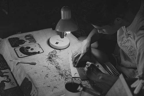 black-and-white grayscale photography of man writing on brown paper near turned on lamp grey