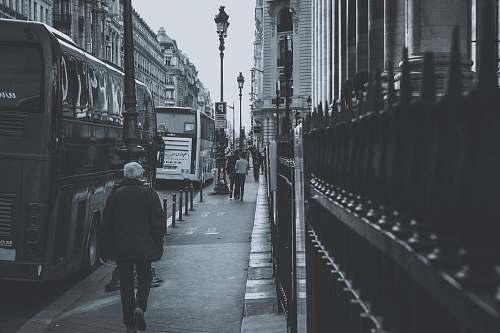 human grayscale photography of people walking on sidewalk grey