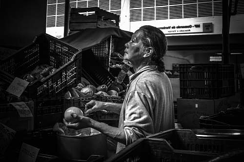 human grayscale photography of woman holding round fruit near crates black-and-white