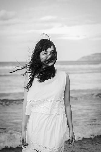 person grayscale photography of woman standing on seashore black-and-white