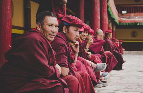human group of men wearing red dress sitting at the temple smiling while taking selfie person