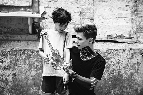 human man and boy looking on guitar in grayscale photo black-and-white