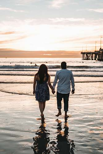 human man and woman holding hands each other while walking on seashore during daytime pier