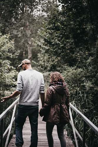 human man and woman holding hands walking on bridge during daytime person