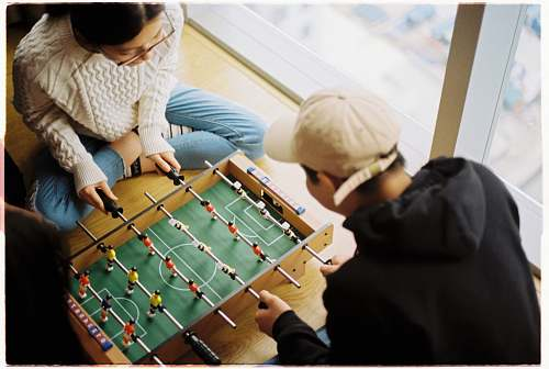 human man and woman playing foosball table person