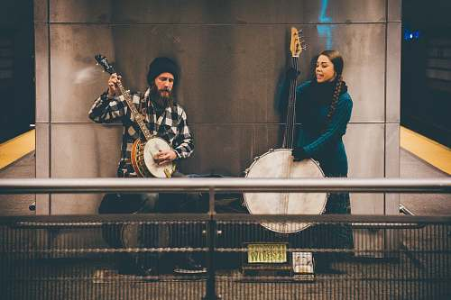 human man and woman playing string instruments standing near wall person