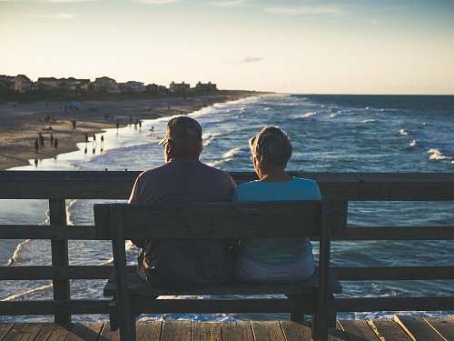 human man and woman sitting on bench in front of beach person