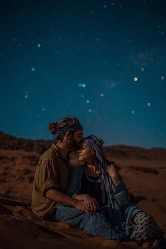 person man and woman sitting on desert sand under blue sky during nighttime human