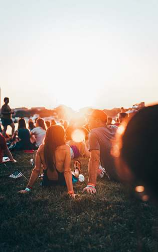 person man and woman sitting on grass surrounded with people during golden hour human
