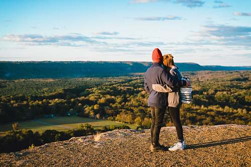 human man and woman standing on mountain cliff in front of green trees person