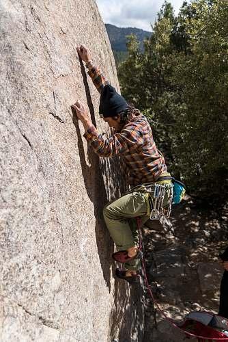 person man climbing on rock during daytime human