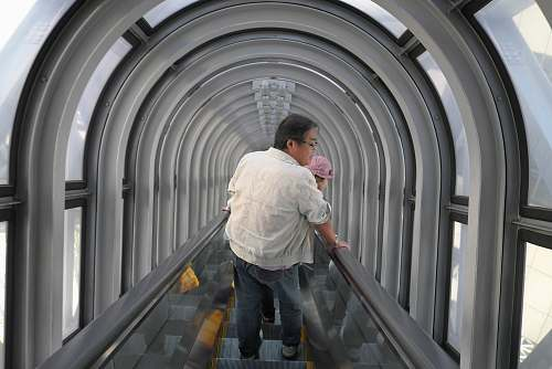 human man holding baby riding escalator person