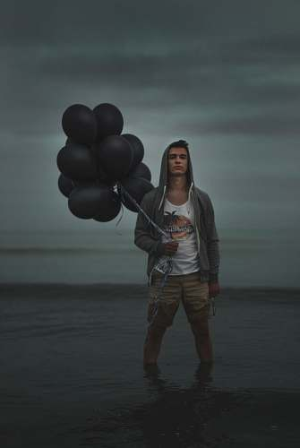 human man holding balloons while on water person