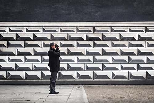 human man holding camera near wall person