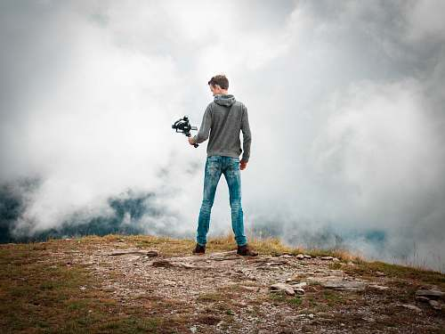 human man holding camera with stabilizer while standing person