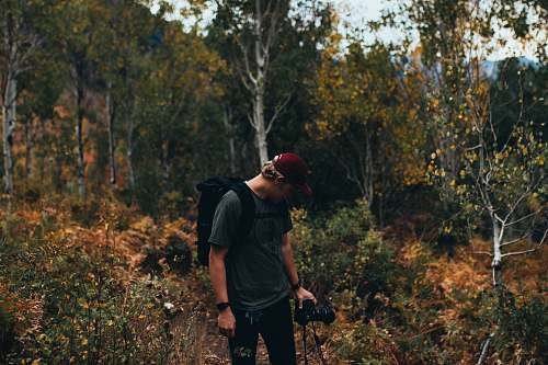 human man holding DSLR camera in the middle of the forest person