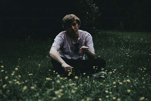 human man holding flower while sitting on green grass field person