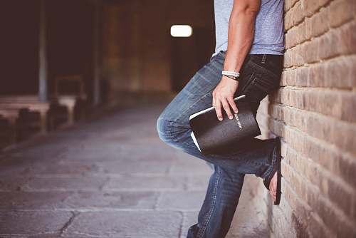 person man holding Holy Bible leaning on bricked wall book