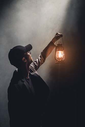 human man holding lighted gas lantern person