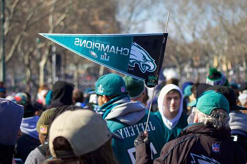 person man holding Philadelphia Eagle pennant crowd