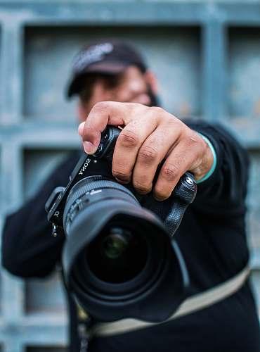 person man holding Sony DSLR camera photographer